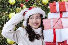 Muchacha alegre que lleva a cabo regalos de Navidad Fotografía de archivo