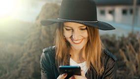 Muchacha alegre que manda un SMS afuera almacen de metraje de vídeo