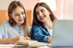 Muchacha alegre que mira a su hermana más joven estudiar Fotografía de archivo libre de regalías