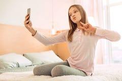Muchacha alegre que muestra la muestra de V mientras que toma el selfie Imágenes de archivo libres de regalías