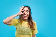 Muchacha alegre que presenta en auriculares Imagen de archivo libre de regalías