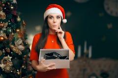 Muchacha alegre que recibe los zapatos planos de plata como regalo de la Navidad foto de archivo