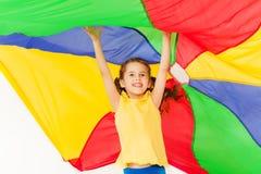Muchacha alegre que salta debajo del toldo hecho del paracaídas Imágenes de archivo libres de regalías