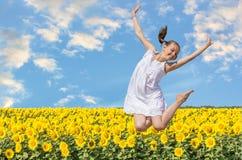 Muchacha alegre que salta en un fondo de girasoles Fotografía de archivo