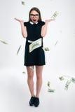 Muchacha alegre que se coloca debajo de la lluvia con los billetes de dólar Fotos de archivo libres de regalías