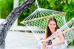 Muchacha alegre que se relaja en hamaca Imagen de archivo libre de regalías