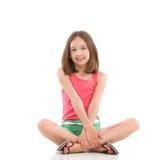 Muchacha alegre que se sienta con las piernas cruzadas Foto de archivo