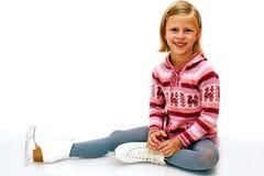 muchacha alegre que se sienta en patines de hielo Foto de archivo