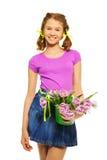 Muchacha alegre que sostiene el cubo con los tulipanes rosados Foto de archivo libre de regalías