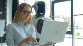 Muchacha alegre que sostiene el ordenador portátil y que habla con la máquina robótica almacen de video