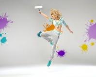 Muchacha alegre que sostiene un rodillo de pintura Foto de archivo