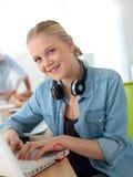 Muchacha alegre que usa el ordenador portátil y los auriculares Imagenes de archivo