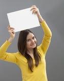 Muchacha alegre 20s que hace un anuncio en el aumento de un parte movible en blanco sobre su cabeza Foto de archivo