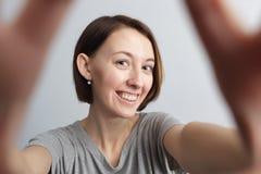 Muchacha alegre sonriente con las pecas que hacen el selfie Estirar el th Fotografía de archivo libre de regalías