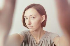 Muchacha alegre sonriente con las pecas que hacen el selfie Estirar el th Imágenes de archivo libres de regalías