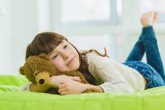 Muchacha alegre y de sueño feliz que sostiene el oso de peluche interior Fotos de archivo