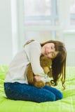 Muchacha alegre y de sueño feliz que sostiene el oso de peluche interior Imagen de archivo