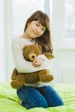 Muchacha alegre y de sueño feliz que sostiene el oso de peluche interior Foto de archivo libre de regalías