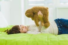 Muchacha alegre y de sueño feliz que sostiene el oso de peluche interior Imagenes de archivo