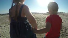 Muchacha alegre y muchacho que corren descalzo en la arena almacen de video