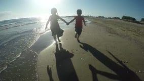 Muchacha alegre y muchacho que corren descalzo en la arena metrajes