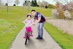 Muchacha alegre y papá que montan una bici Fotografía de archivo