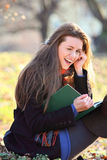 Muchacha alegre y sonriente que lee un libro en el parque Imagen de archivo libre de regalías