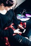 Muchacha alternativa joven que se sienta en el piso negro con una escuela Fotos de archivo libres de regalías