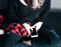 Muchacha alternativa joven que se sienta en el piso negro con una escuela Imagen de archivo