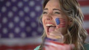 Muchacha americana feliz que anima con sonrisa en cara, candidato favorable, elecciones metrajes