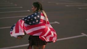 Muchacha americana orgullosa que detiene a las barras y estrellas Ella envuelve la bandera americana sobre sus hombros y camina a almacen de video