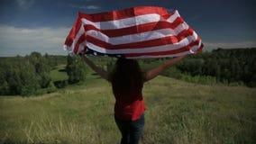 Muchacha americana orgullosa que detiene a las barras y estrellas en la cámara lenta metrajes