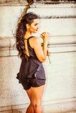 Muchacha americana que le falta con la rosa del blanco que se coloca en el st del vintage Foto de archivo