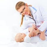 Muchacha amistosa joven sonriente del doctor Examining Cute Kid de la mujer. Imagen de archivo libre de regalías