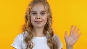 Muchacha amistosa que agita su mano, feliz de verle, fondo amarillo aislado metrajes