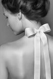 Muchacha apacible hermosa con el arco de seda en la parte posterior Fotografía de archivo libre de regalías