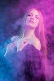 Muchacha apasionada hermosa en el humo Imagen de archivo