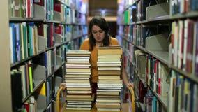 Muchacha apenada que busca para los libros almacen de metraje de vídeo