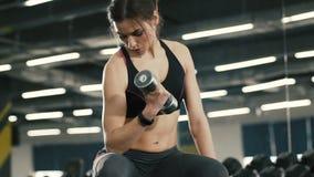 Muchacha apta con pesas de gimnasia en el fondo del gimnasio almacen de video