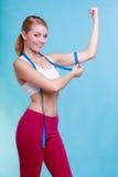 Muchacha apta de la mujer de la aptitud con la cinta métrica de la medida su bíceps Imagenes de archivo