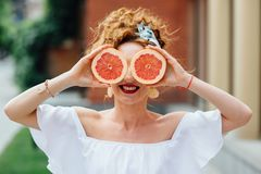 Muchacha apta de la mujer que sostiene dos halfs de pomelo Fotografía de archivo