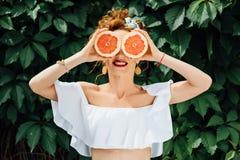 Muchacha apta de la mujer que sostiene dos halfs de pomelo Imagenes de archivo
