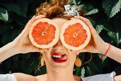 Muchacha apta de la mujer que sostiene dos halfs de pomelo Foto de archivo libre de regalías