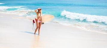 Muchacha apta de la persona que practica surf en la playa Imágenes de archivo libres de regalías