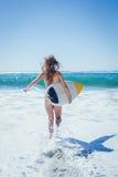 Muchacha apta de la persona que practica surf que corre al mar con su tabla hawaiana Imagen de archivo