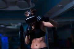 Muchacha apta del boxeador joven del combatiente en los vidrios de VR que llevan guantes de boxeo Fotografía de archivo
