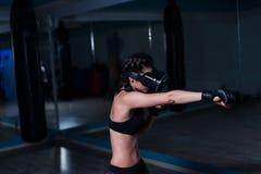 Muchacha apta del boxeador joven del combatiente en los vidrios de VR que llevan guantes de boxeo Imagen de archivo