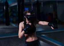 Muchacha apta del boxeador joven del combatiente en los vidrios de VR que llevan guantes de boxeo Imagen de archivo libre de regalías