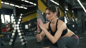 Muchacha apta que hace ejercicios en el fondo del gimnasio almacen de video