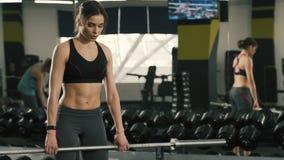 Muchacha apta que hace ejercicios en el fondo del gimnasio metrajes